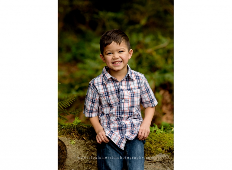 Smiling boy sitting on log UW Arboretum | Lynnwood Family Photographer
